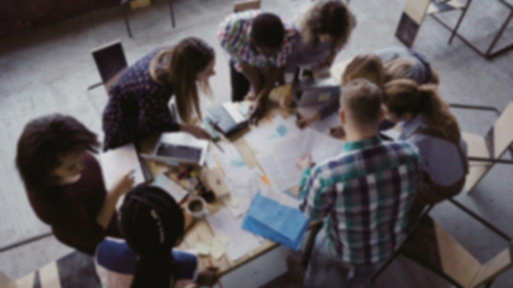 A group of millennials sit around a large desk at work