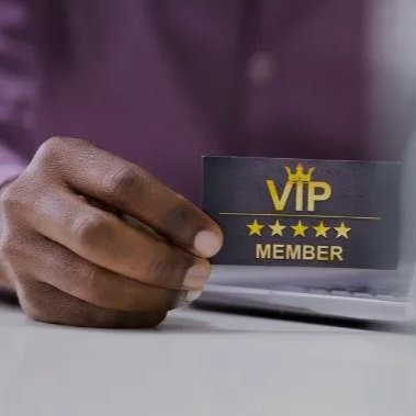 A hand proudly holds a black VIP member card between finger and thumb