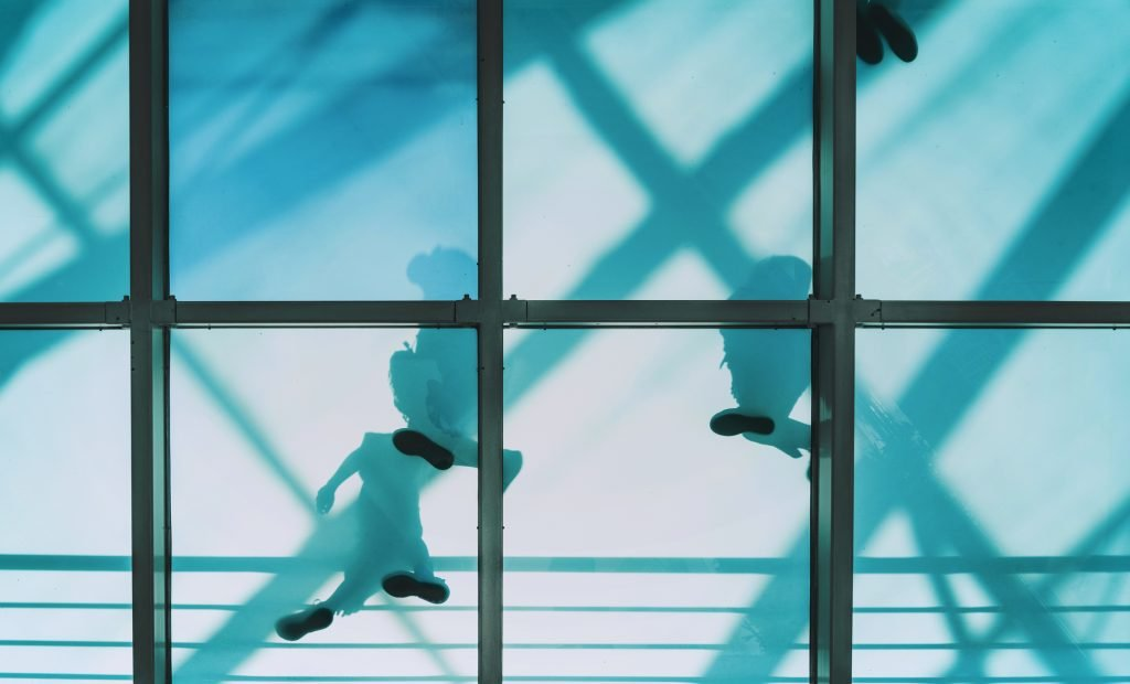 Shadow figures move above a transparent pedestrian bridge