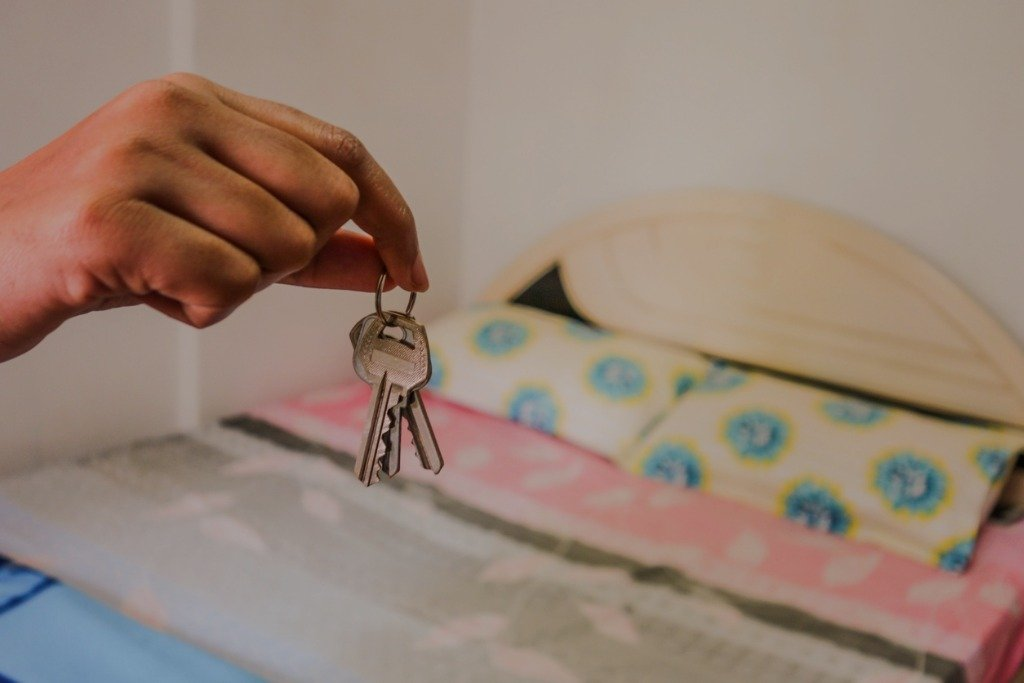 A hand holds a set of keys above a neatly made bed