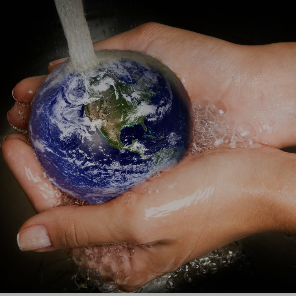 Cupped hands hold a small model of the world under a running tap