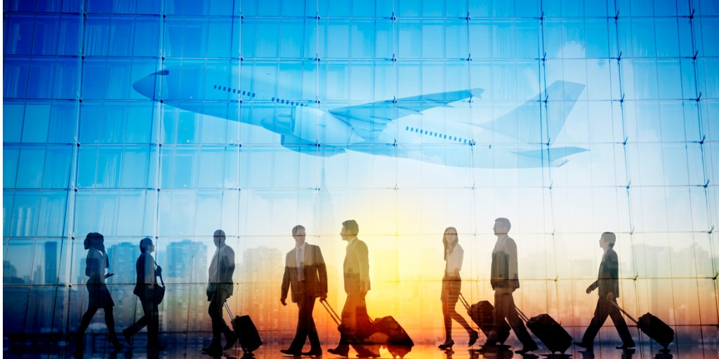 Business travellers walk through a glass airport terminal as a plane ascends and the sun rises, hinting at the future of business travel