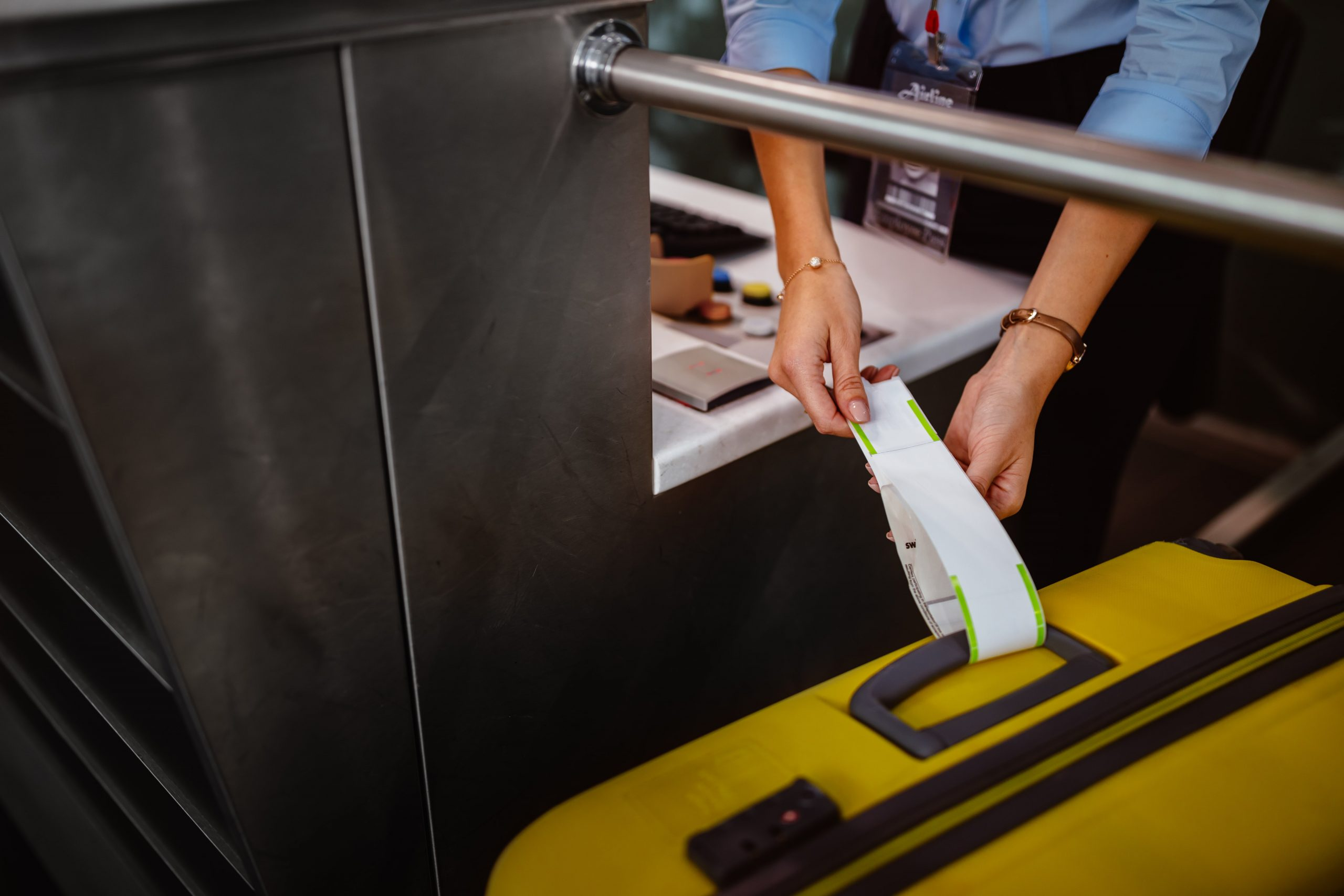 Airport check-in officer tags a large suitcase for travellers longer stay