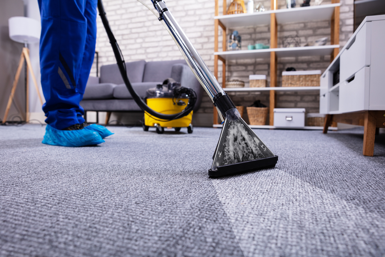 Professional cleaner hoovers carpet in a serviced apartment wearing personal protective clothing against spread of COVID-19